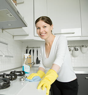 young-smiling-woman-wearing-rubber-gloves-cleaning-stove (2)